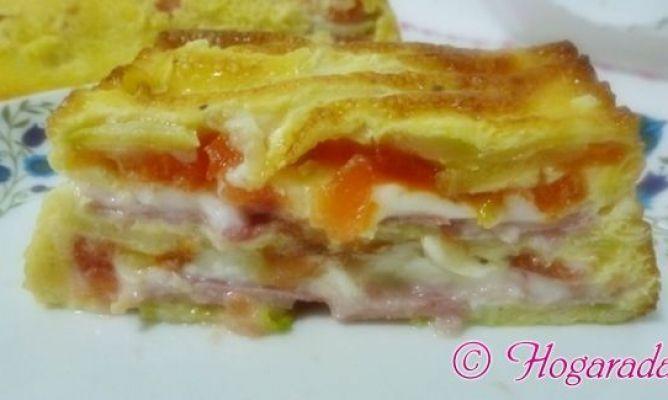 Ingredientes:   1 calabacín mediano   1 tomate grande   6 lonchas de queso de sandwich   6 lonchas de jamón de york   3 huevos medianos   Sal   Pimienta   Elaboración:   Lo primero que haremos será lavar el calabacín y pelarlo. No os preocupéis si os queda algo de verde, le dará un toque también muy bonito de color. Lavamos también el tomate, lo pelamos, lo cortamos en rodajas finas y lo reservamos. Ahora cortamos el calabacín en rodajas. En la receta original lo hacen con mandolina, yo a…
