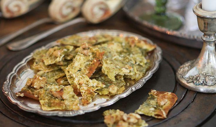 Sätt ugnen på 200 grader. Lägg brödskivorna på en plåt. Bred pesto i ett jämnt lager ovanpå. Strö över den rivna osten och valnötterna. Gratinera i ugnen ca 10 minuter. Bröden ska bli gyllenbruna. Ta ut ur ugnen, låt svalna och bryt sedan bröden i mindre bitar.