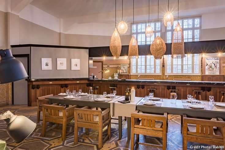Dans la salle à manger de l'ancienne Poste de Trouville, une large table en bois massif trône au milieu de la salle à manger où les hôtes se retrouvent pour des repas conviviaux. Au-dessus de la table, des suspensions en maille de fer.
