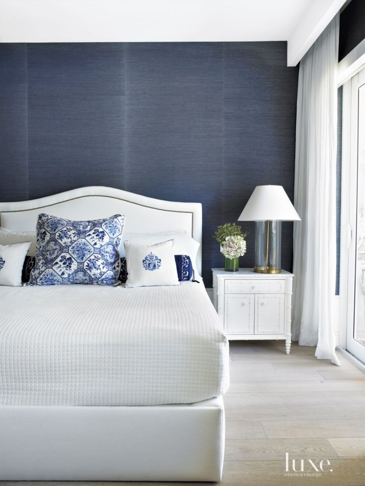 Marine blue grass-cloth wallpaper by Phillip Jeffries creates a sense of intimacy in the master suite. The bed, by Williams-Sonoma Home, faces the water view, seen through draperies from iDesign Miami. The bedside table and lamp are also by Williams-Sonoma Home.
