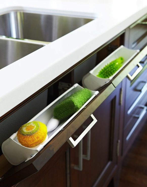 Great use of dead space with hidden sponge cabinet located below kitchen sink. Hidden pull-out panel below kitchen sink housing kitchen sponges and accessories.