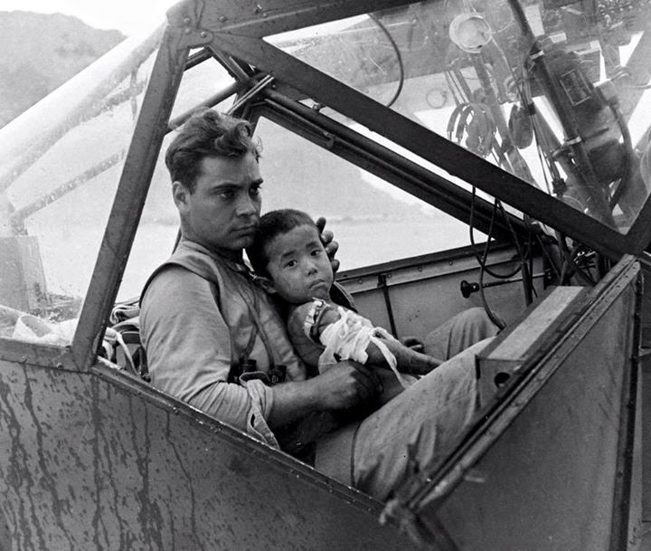 US soldier cradles a wounded Japanese boy in a cockpit during the Battle of Saipan 1944. Photo by Peter Stackpole.
