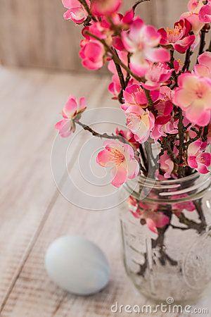Cherry Blossom-takken in de vaas van de glaskruik met pastelkleur blauwe Easte