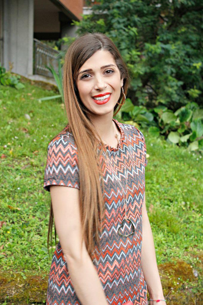 Un outfit dai colori dell'alba con focus su un minidress dalla stampa geometrica arricchito da accessori colorati.