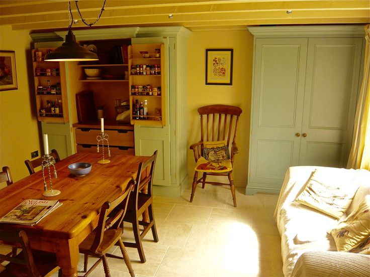 A cosy, country kitchen. In the corner is an open Pantry Cupboard with spice racks fitted to the back of the doors.