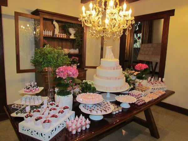 Linda mesa decorada por Gardênia Araújo Festas, com armário de madeira ao fundo. Um luxo!