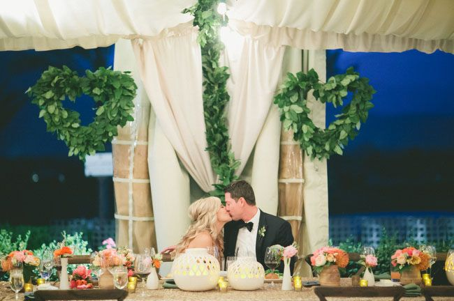 Heart wreaths made of greenery hanging above the sweetheart table
