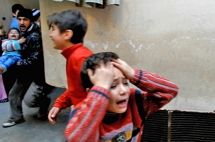 A man runs carrying a toddler as children weep during fighting in the Bab Tudmor neighborhood of the restive city of Homs, some 160kms north of the Syrian capital Damascus on February 25, 2012.