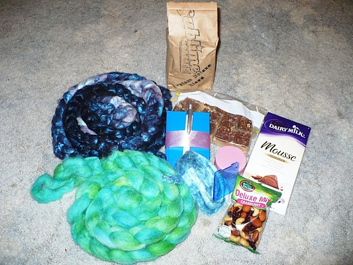 "MelindaJane from ShannynM: ""Purpley / Blue fibre - 66% Merino 33% Silk, green fibre - Texel, Blue - Hand Dyed Silk, Gauge thingy :), Notebook & Pen, Beautifully scented rose soap.Treats: PB Slice (no it didnt melt - but it wont last long the way its looking at me), Yummy mix of nuts & cranberries, Chocolate Mousse (YUMMMM!!), and Coffee Beans ….aaaahhhhh…Heaven!"