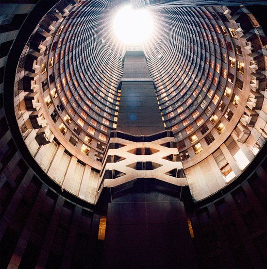 Ponte Tower, the 54-storey-high concrete tube that has soared over the skyline of  Johannesburg since 1975. In the midst of the South African Apartheid, Ponte City was emblematic of the country's dehumanising system of racial segregation. Here, only wealthy white families were allowed to live in the outward-facing apartments, while the tube's inner apartments  were reserved for their black servants, who lived in permanent gloom.