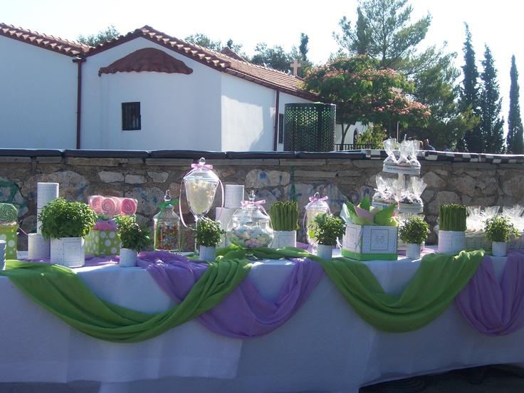 Μεγάλο τραπέζι για το στολισμό της βάπτισης με μπομπονιέρες, βασιλικούς, γλειφιτζούρια, κουφέτα και υφάσματα.