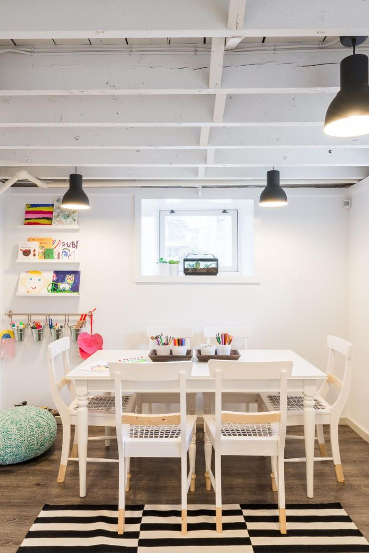 This fun art studio for kids was created by Justine Sterling in the low-ceiling basement of a 1920s Colonial. The transitional room features contemporary cabinets and furnishings, and the rafters were exposed and painted white to create a feeling of greater space.