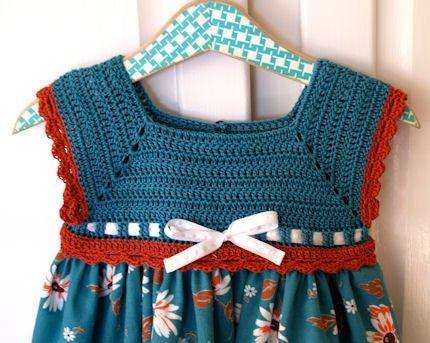 A surprisingly pretty match of vintage daisies on a teal background joined by modern day polka dots.    The bodice is hand crocheted in 100% cotton teal yarn with scalloped edging around the armholes and bodice bottom in rust. The dress skirt is 100% pre-washed vintage cotton with a banding/hem in modern polka dots in shades of teal, rust and green on a white background. Pretty shades of teal vintage cat eye plastic buttons and white-on-white polka dot ribbon add to the lovely details of...