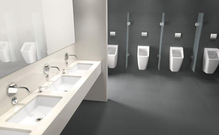 Aseos públicos. Decoración minimalista y funcional en donde predomina el color blanco de base de las piezas de cerámica tanto de lavabos como de sanitarios. Combina con suelo gres y azulejos grises. Grifería de diseño y amplio espejo decorativo. Iluminación lámparas de luz blanca (tubos fluorescentes).