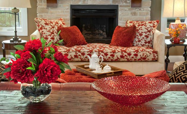 This bright #scarlet hue is carried throughout the room through floral arrangements, #artwork, a table #lamp and #upholstery on the #ottoman and tufted leather couch. A cheerful cherry blossom pattern draws the eye to the room's showstopper piece—an unusual settee from Lexington Furniture. #housetrends #omgrooms