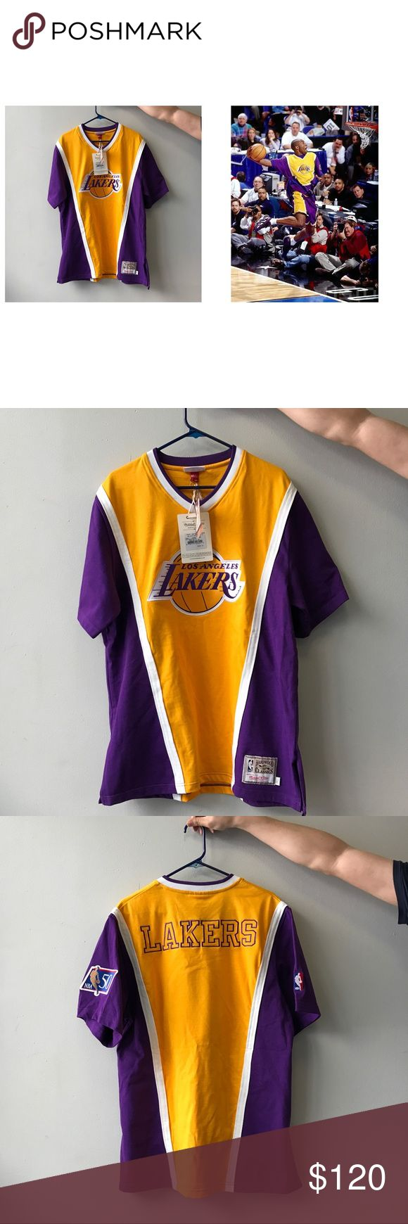 Los Angeles Lakers authentic shooting shirt. Size: 44 Large. Brand new! 🌟Kobe wore this T-shirt on 1997 All-star Slam Dunk Contest.🌟Wear the Lakers with a classic look in this 1996 Authentic Shooting Shirt from Mitchell and Ness. Features a tackle twill LA Lakers Primary logo on the front with the Lakers team name embroidered on the back. Made of 60% Cotton and 49% Polyester. 🌟Bought from lakersstore.com. I bought a wrong size for my family so I want to sell this. Mitchell & Ness Suits…