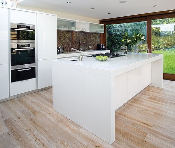 by Glenvale Kitchens  Contemporary furniture trends have used us to a mixture of functional and stylish: this is exactly what this kitchen is about. Sleek white combined with middle-hued warm wood is probably the most popular modern combination when it comes to finishes. There's a hint of nature and the artifice of functionality – the best of both worlds in a comfortable kitchen layout, while the wire chairs bring some design culture into play. Notice how pretty much all kitchen islands use…