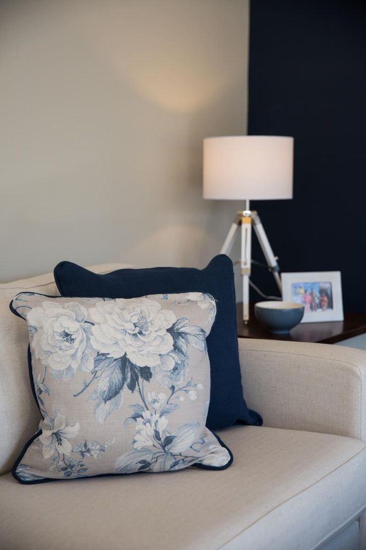 Colour is brought to life through more than just a painted feature wall. It's important to consider the fabrics in your scheme, we love the blue accents in this floral cushion it brings together the overall look in our Henley show home.