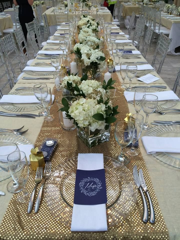 "Table setting one for ""Glittering Gold"". Gold sequins runner, glass underplates, white napkin with menu placed on top. Flowers arrangements are white hydrangeas with gold gyp and little elements of green."