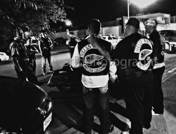 Hells Angels taunt RCMP officers in downtown Kelowna, British Columbia, Canada a few years ago. #garymoorephotography #realworldphotographs #kelowna #photojournalism #canada #hellsangels #photojournalist #bikers #gangs