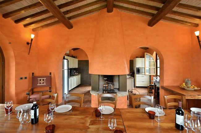 Our welcoming osteria (tavern), painted a warm orange colour, is at the exclusive disposal of the guests staying at the villa if they want to have any of their meals there.  The dining room looks onto the open-plan kitchen, being separated from it only by the fireplace between two archways, as well as the countryside through the ample windows.