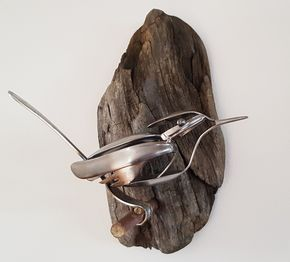 Bird made from recycled stainless steel spoons and forks on driftwood backing.