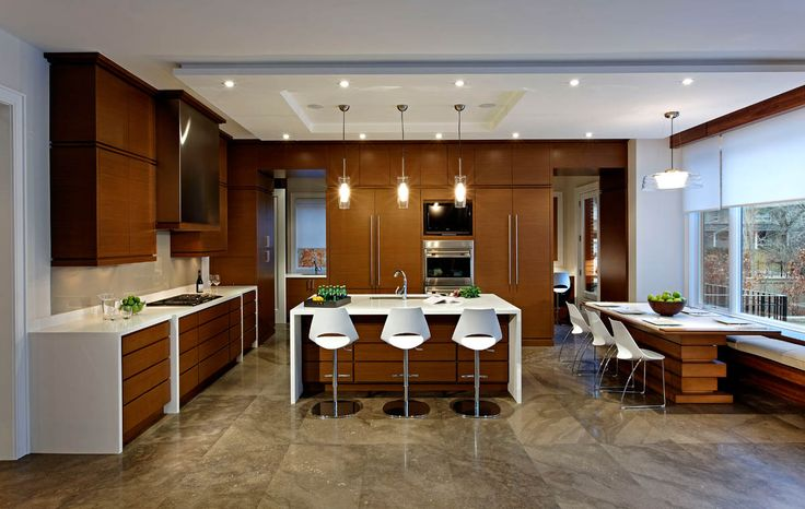 "The limestone flooring pattern is made even more prominent by the contrast with the simplicity of the kitchen cabinetry. The ceiling detail, ""stacked and wrapped"" counter units and breakfast table reflect the layering and sculpting throughout the home.  #kitchen #design #luxury #island #kitchenisland #breakfast #breakfasttable #custom #luxury #limestone #ciot #stonetile #walnut"
