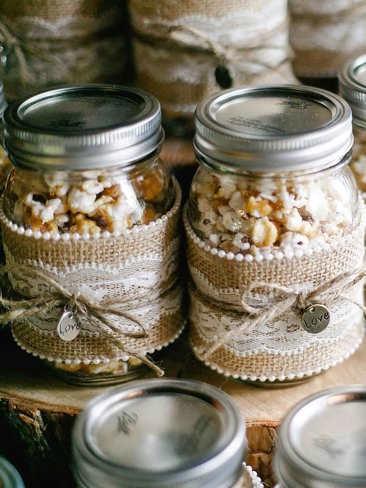Wrap mason jars with lace and burlap decorations for rustic wedding favors that present caramel popcorn favors in a fashion-forward way.