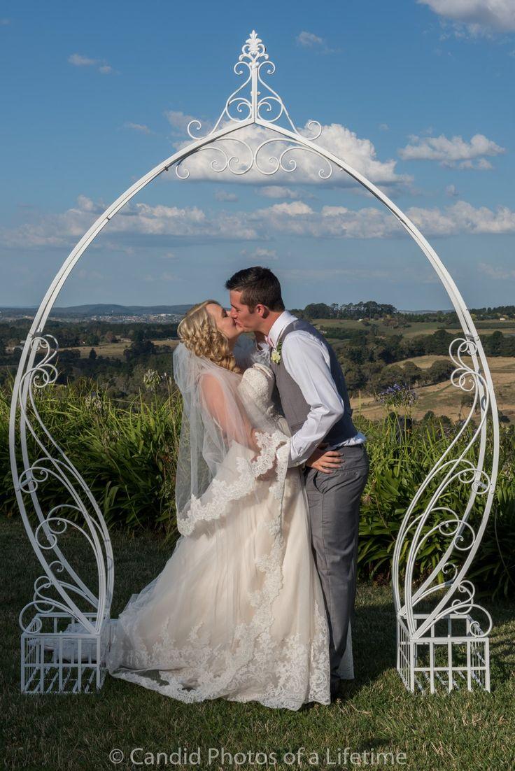 Candid Photos of a Lifetime - Kiss under an arch - what a beautiful fairytale wedding for this couple  Borrodell Vineyard, Orange www.candidphotosofalifetime.com.au