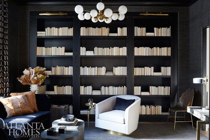 Swathed in Sherwin-Williams' Caviar, this inky library strikes a moody chord. The sofa and chair are through Bradley, and the coffee table and desk are by Julian Chichester.