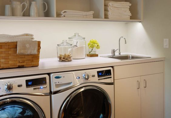 Streamlined laundry room with white side by side front loading washer and dryer below flat front cabinets accented with nickel hardware below a small stainless steel sink framed by white counters and open cubby shelves above.: