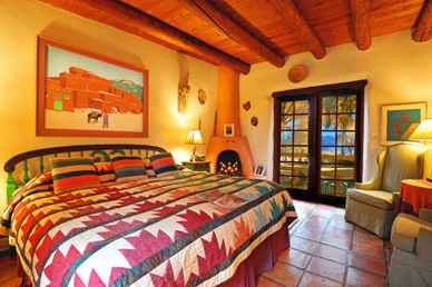 La Vista Room  Located in the same adobe casita as El Pueblo, this room with soft southwestern colors has a king size bed, corner candlelit fireplace, and French doors that open out to a wide expanse of lawn and gardens with a grand view of sacred Taos Mountain.