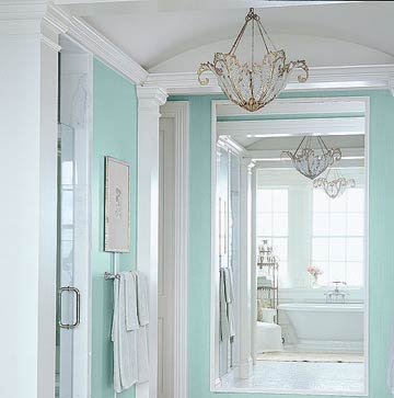 Crystal beaded chandeliers hang at opposite ends of this mirrored bathroom hall, creating gorgeous repetition.