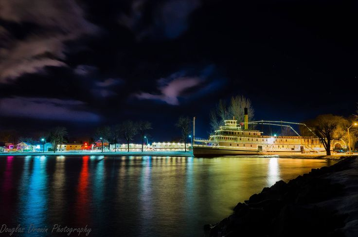 Stern Wheeler SS Sicamous at Night, by Landscape Photographer Douglas Drouin. Ship is outlined in hundreds of tiny white lights, and coloured light is reflected on the calm surface of the lake. Photo location: Penticton, Okanagan, BC, Canada.