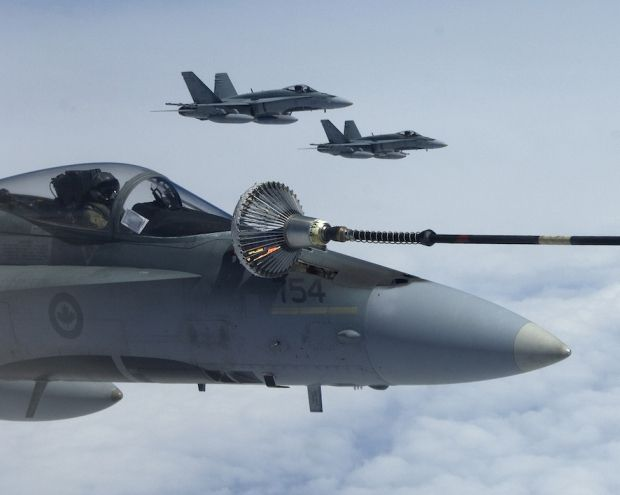 Royal Canadian Air Force Boeing CF-18A/B Hornets, taking turns for a drink.