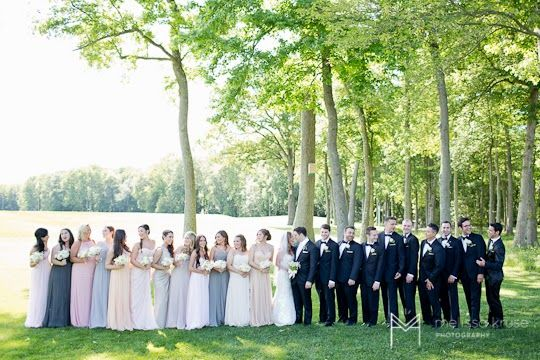 Bridesmaid and Groomsmen photo with women in pink, grey and nude and men in tuxedos with black bow ties. Black Tie Optional on golf course