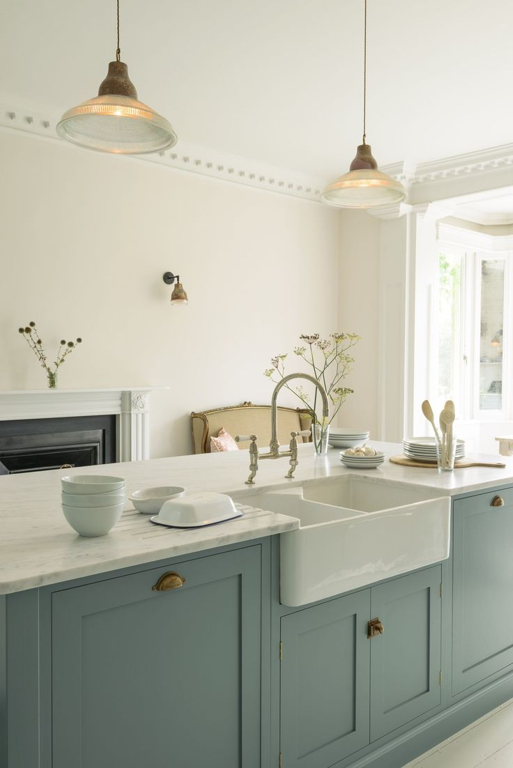 Honed Carrara marble worktops, a huge double Belfast sink, chrome taps and brass hardware