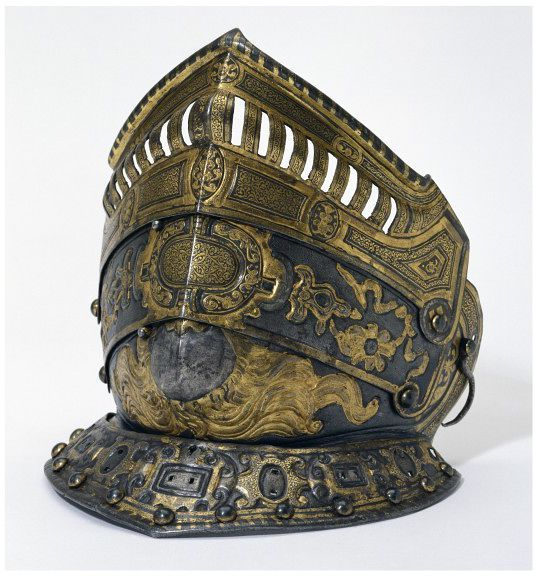 This piece comes from a burgonet (French bourguinotte), a type of lightweight helmet with a peak, tall comb and cheek-pieces that first appeared in Italy in the early 16th century. The lavish decoration and the thinness of the metal on the buffe suggest the burgonet was primarily a parade helmet, rather than a protective battle helmet. #armor