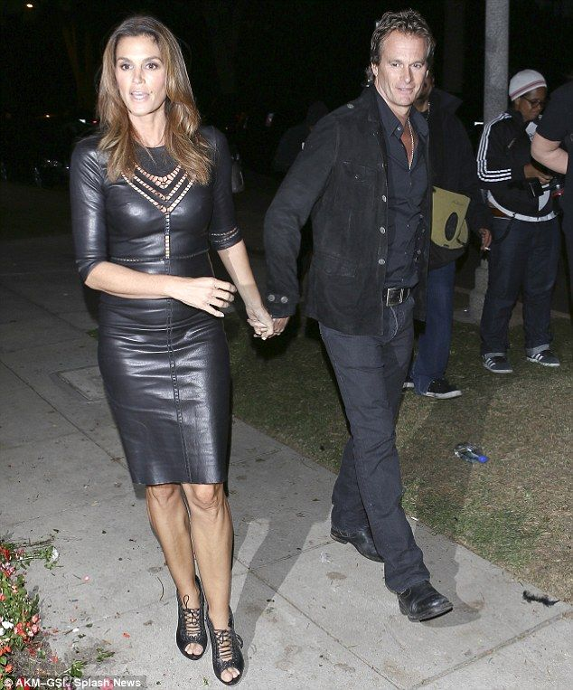 Cindy Crawford in jaw-dropping leather dress with sexy high heels. Great legs and curves on display in the figure hugging dress.