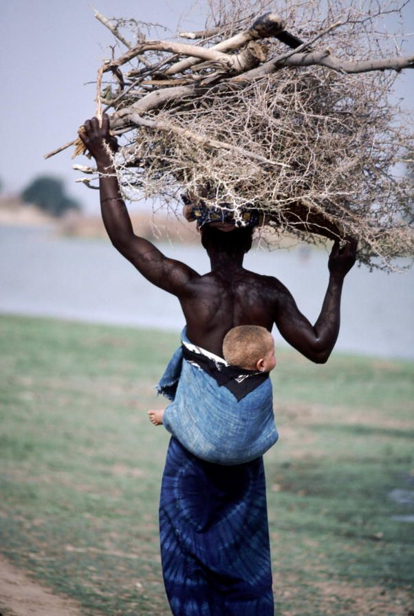 Africa | Mali.  Woman with an albino baby carrying firewood in Segou.