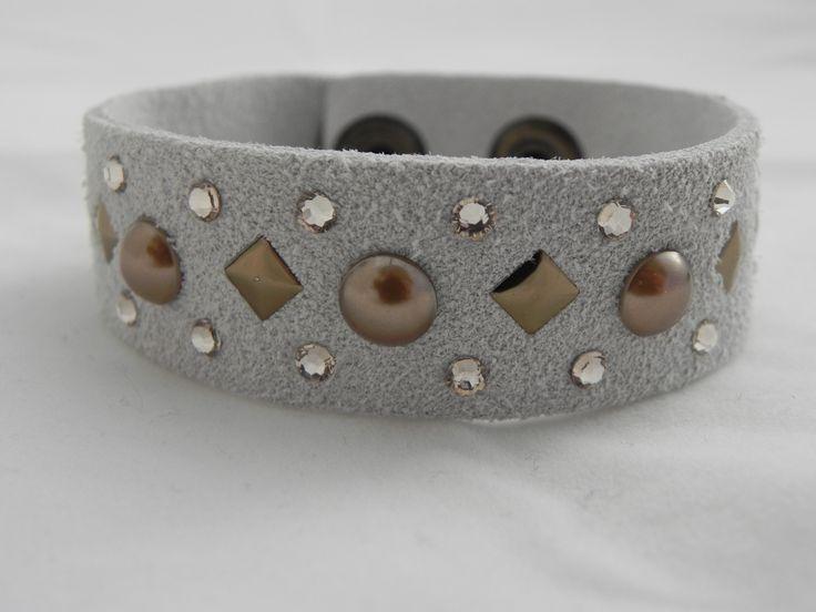 Bracciale in camoscio decorazioni Swarovski Bracciale donna/unisex con base in camoscio e applicazioni in cristalli e perle Swarovski.Il Bracciale è alto 20 mm e lungo nel totale 20 cm, l'allaccia...