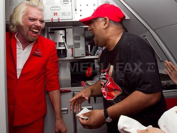 """Richard Branson, """"stewardesă"""" pe un zbor Air Asia pentru a onora un pariu cu Tony Fernandes"""