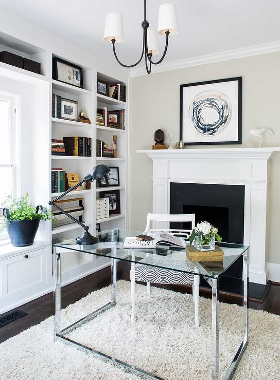 chic office features a reed small chandelier hangs over a glass and stainless steel desk chic home office features