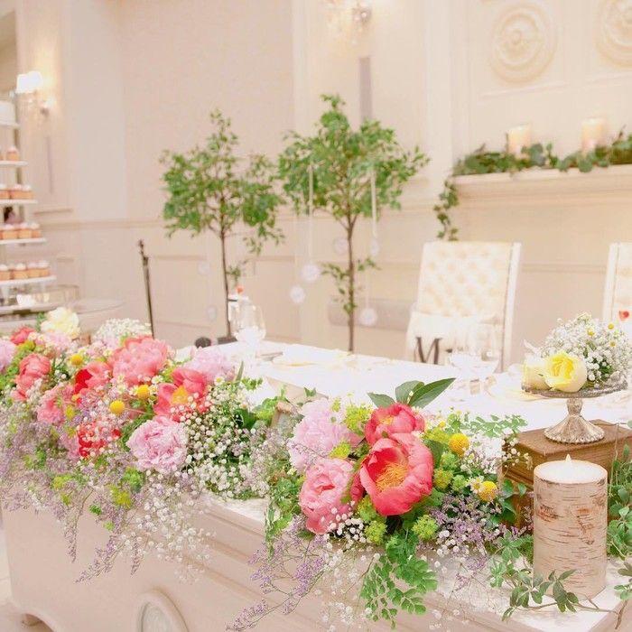 シャクヤク、ソリダコ、かすみ草、マトリカリアなどのお花で飾られたご新婦さまお気に入りの高砂。招待状のデザインにもシャクヤクを取り入れたので、装花にもシャクヤクを使って統一感を出されたそうです。