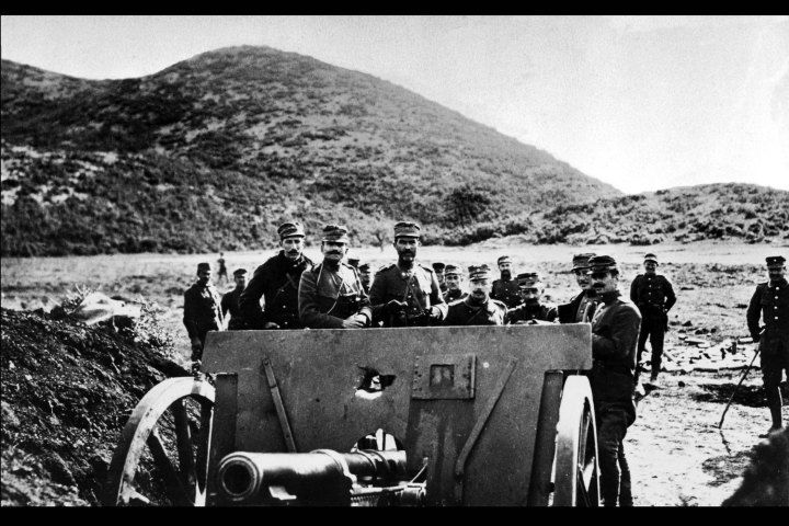 A group of Greek soldiers gather around a large gun on a barren hillside in a photo dated from 1913.