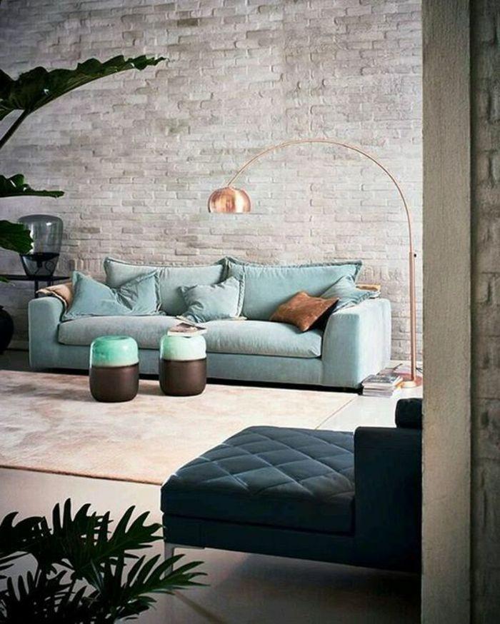 intérieur minimaliste, deux petits tabourets, sofa bleu, lampadaire cuivré, mur en briques
