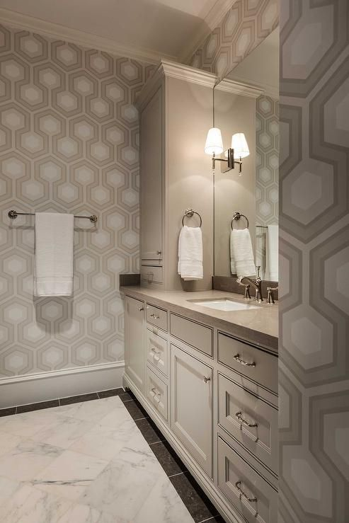White and beige bathroom features walls clad in white and beige hex wallpaper, Hicks Hexagon Wallpaper, lined with a light beige extra wide single washstand topped with taupe stone under a frameless mirror flanked by cabinets.
