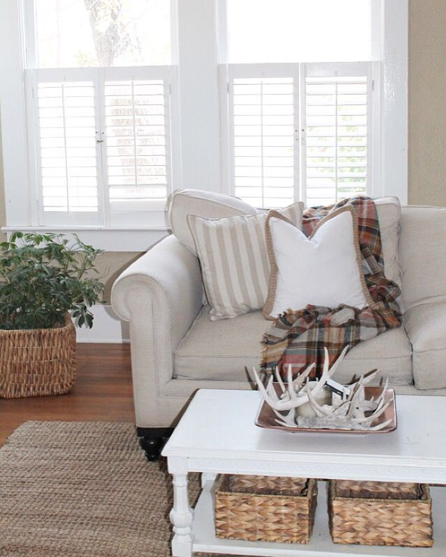 Fall thanksgiving blanket scarf plaid throw pillows white couch jute rug coffee table antlers decor plants copper