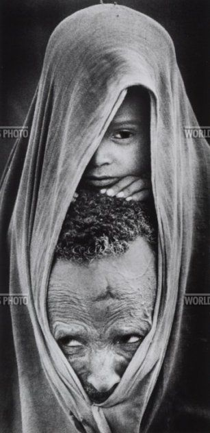Carol Guzy, Ethiopia, 1985. A father and his son try to keep warm in the morning chill as they queue for food at a refugee camp. The boy's mother had died of starvation.