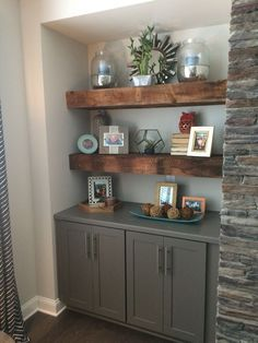 Our beautiful reclaimed wood floating shelves. Flanking fireplace with grey base cabinets located in family room.